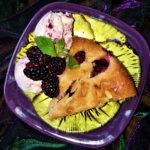 Indian summer almond plum cake with corn and blackberry ice cream on flower plate