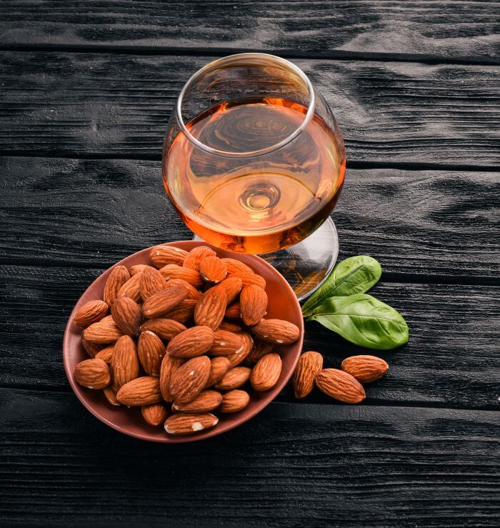 amaretto liqueur in a snifter with almonds in bowl
