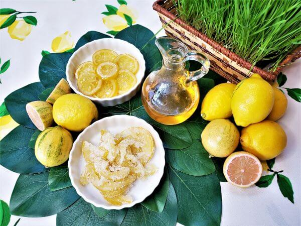 candied lemons and lemon syrup on a green leaf mat with fresh lemons