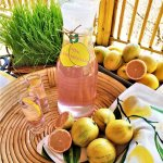 perfectly pink limoncello in carafe with lemons on a table outdoors