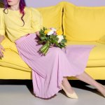 women in pink skirt and yellow top on yellow couch