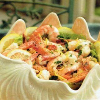 pickled shrimp and lemon slices in white shell bowl