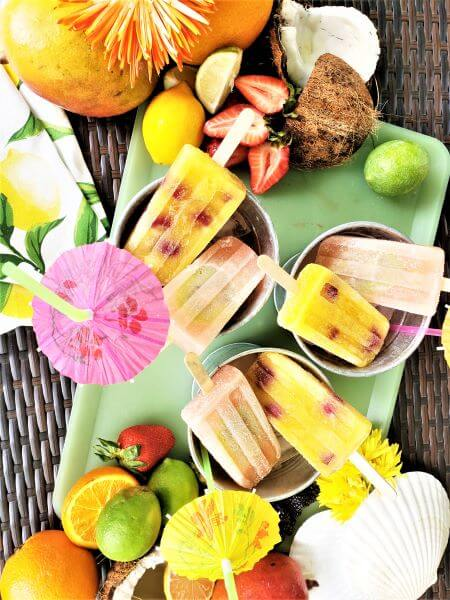 fruity and frosty popsicles in silver bucket with umbrella straws