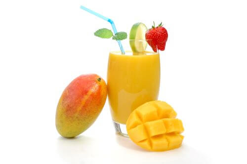 mango nectar in a glass with a cut mango