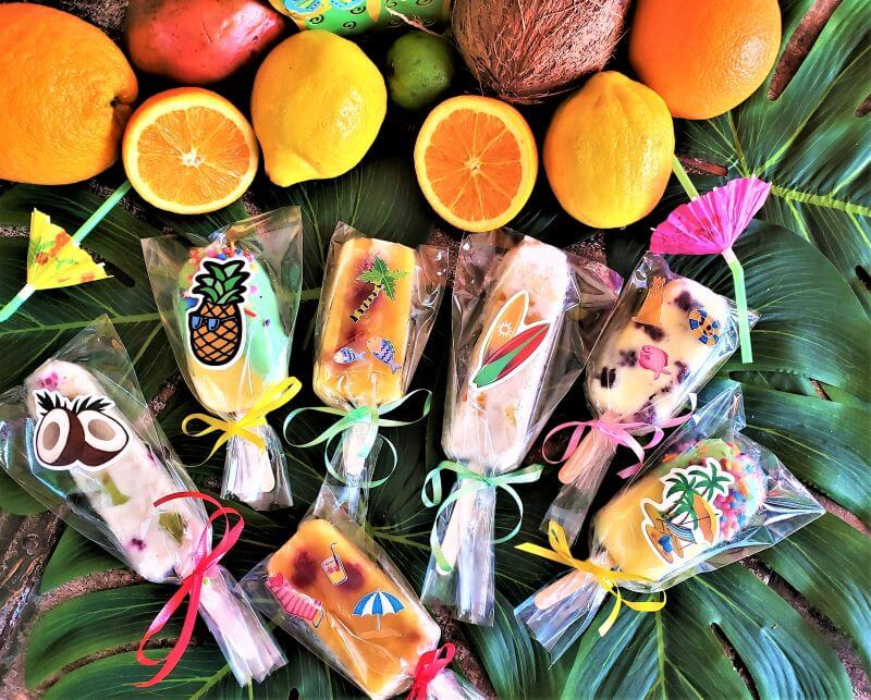 decoratively wrapped popsicles with fruit on palm leaves