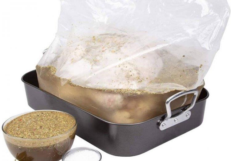 large turkey brining bag with raw turkey in roasting pan