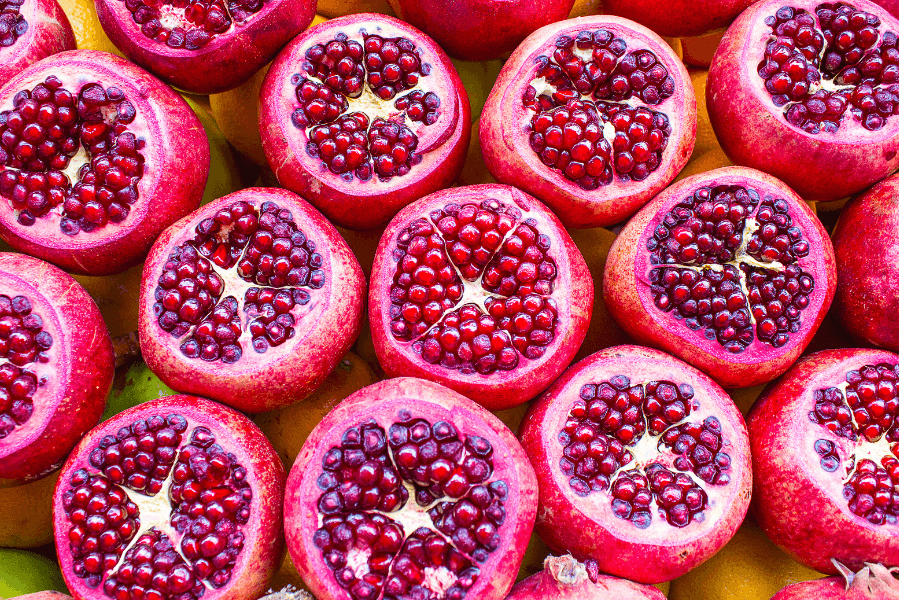 pomegranates with tops cut off to show seeds