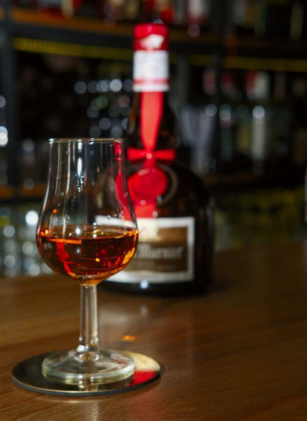 grand marnier in a glass with bottle in background