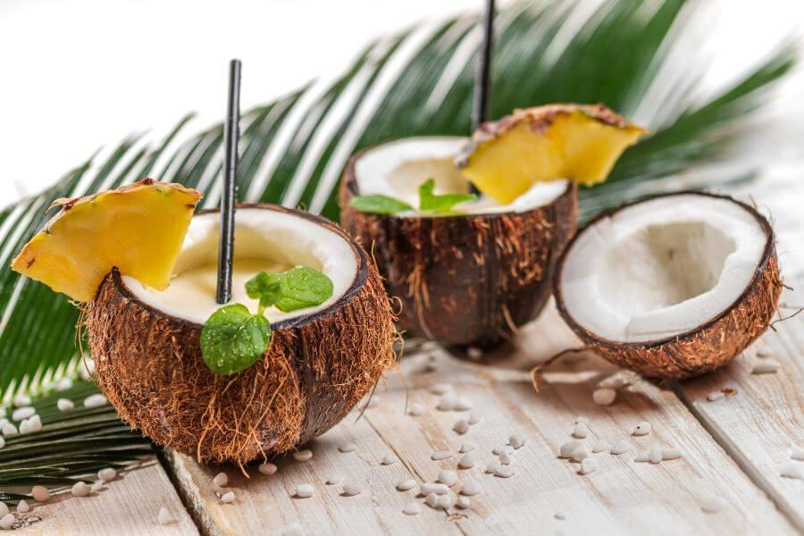 pina colada cocktail served inside coconut half
